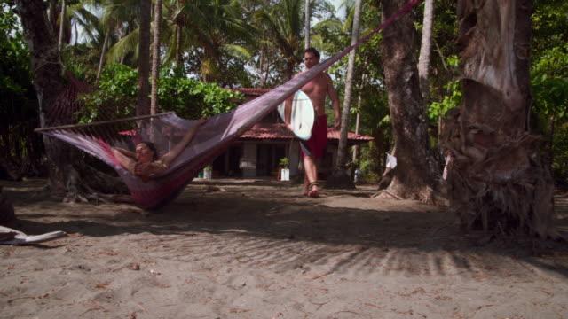 vidéos et rushes de man holding surfboard kisses woman swinging in hammock - embrasser sur la bouche