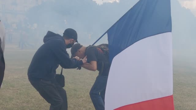 man holding the french flag coughs as tear gas is released by riot police as crowds of protesters demonstrating scatter in the city center near the... - violence stock videos & royalty-free footage