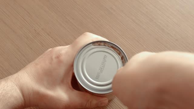 ココナッツクリームでスズ缶を持って開いた男、フラットはクローズアップ - ボトルオープナー点の映像素材/bロール