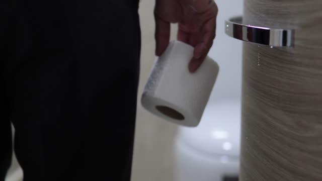 vídeos de stock e filmes b-roll de man holding toilet paper roll in bathroom - assento