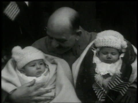montage man holding two babies and two tiny american flags / new york new york united states - 1913 stock-videos und b-roll-filmmaterial
