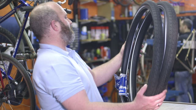 man holding tyre in workshop - greater london stock videos & royalty-free footage