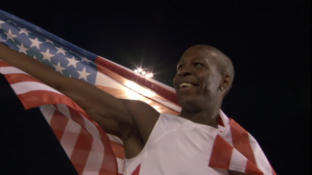 LA MS Man holding up American flag after winning track and field event/ Sheffield, England