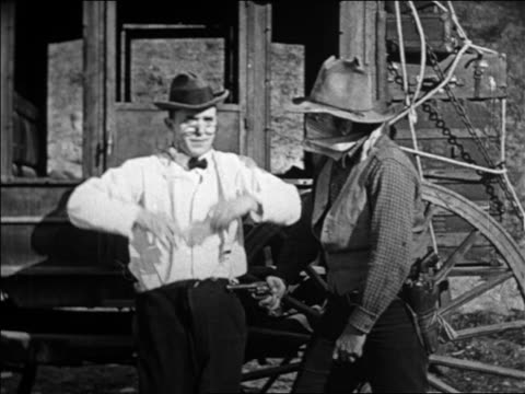 vidéos et rushes de man holding up arms in stagecoach hold-up + pants fall down / feature - 1924