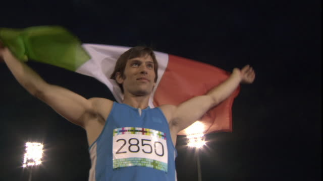 la ms man holding up italian flag after winning track and field event/ sheffield, england - italienische flagge stock-videos und b-roll-filmmaterial