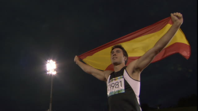 la ms man holding up spanish flag after winning track and field event track event/ sheffield, england - スペイン国旗点の映像素材/bロール