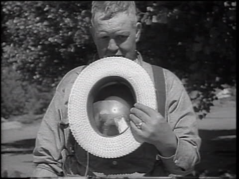 b/w 1937 man holding up straw hat with tiny spinning fan for camera - straw hat stock videos & royalty-free footage