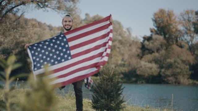 mann hält usa-flagge! - spruchband stock-videos und b-roll-filmmaterial