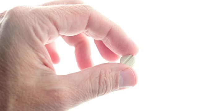 man holding with an antibiotic pill in his hand. - anti impotence tablet stock videos & royalty-free footage