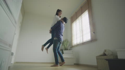 man holding woman near moving boxes - mid adult couple stock videos & royalty-free footage