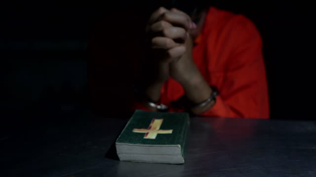 man holds a bible and handcuffs - prison jumpsuit stock videos & royalty-free footage