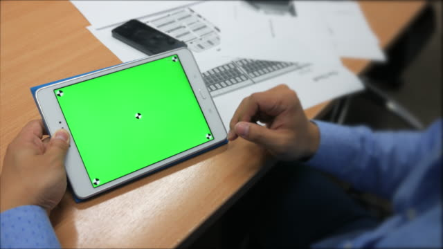 A man holds a blank tablet PC with a green screen