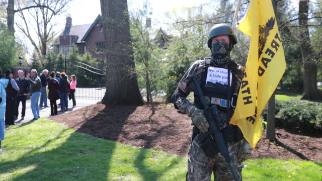 man holds a flag reading, don't tread on me, and holds an ar style rifle that looks much like an m16, outside the governor's house. protesters gather... - street style点の映像素材/bロール