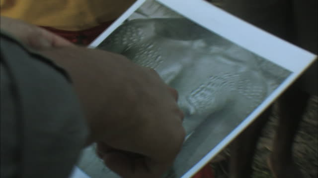 stockvideo's en b-roll-footage met a man holds a photograph that depicts men with ornate body art and tattoos. - men