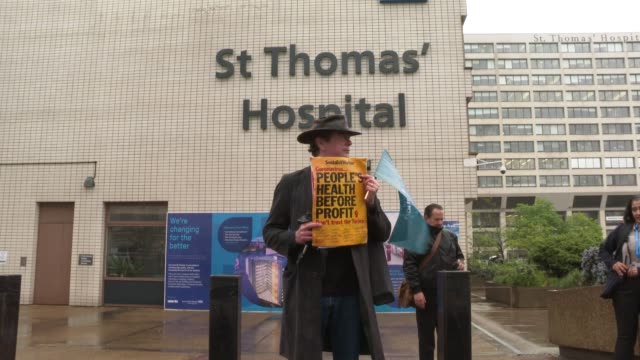 a man holds a placard that reads people's health before profit outside st thomas hospital as he attends a minute's silence on april 28 2020 in london... - placard stock videos & royalty-free footage