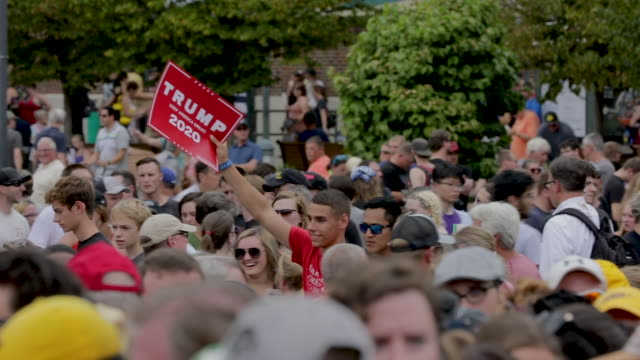 man holds a trump campaign sign as he walks past the des moines register political soapbox where twenty-two of the 23 politicians seeking the... - agricultural fair stock videos & royalty-free footage