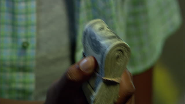 A man holds a wad of dollar bills then a man takes it from his hand but the first man gets the money back.