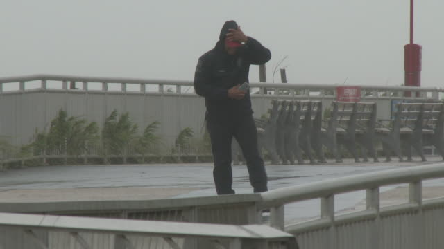 a man holds onto his cell phone in one hand while holding onto his hat with his other hand in wind driven torrential rain on rockaway beach during... - scott mcpartland stock videos & royalty-free footage