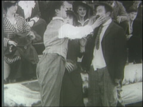 B/W 1914 man holds other man's face slaps him into crowd