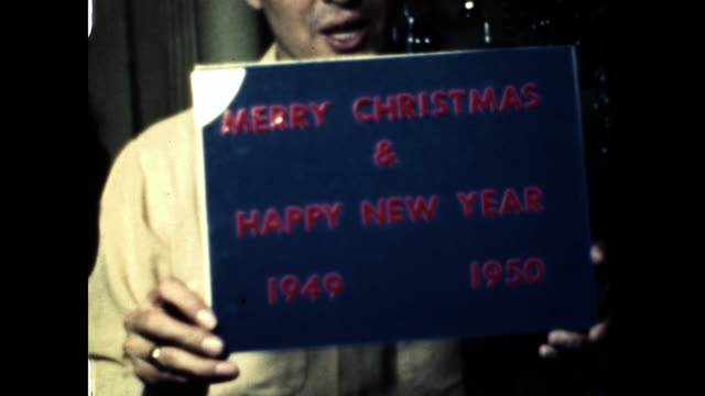 "man holds sign that reads ""merry christmas & happy new year 1949, 1950."" - 1940 1949 stock-videos und b-roll-filmmaterial"
