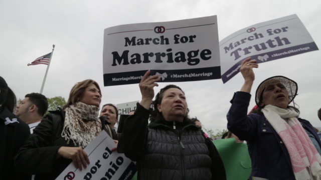 Man holds sign that says Marriage = 1 Man and 1 Woman Only People pray hold signs and rally in front of the US Supreme Court