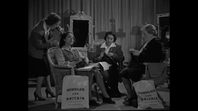 vídeos de stock e filmes b-roll de man holds slate in front of actresses ô bundles for britain publicity merle oberon' / oberon in dressing room chair knits as her hair is styled two... - atriz