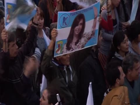 a man holds up a poster of argentina president cristina fernandez' in may square during the celebrations of her reelection - poster stock videos & royalty-free footage