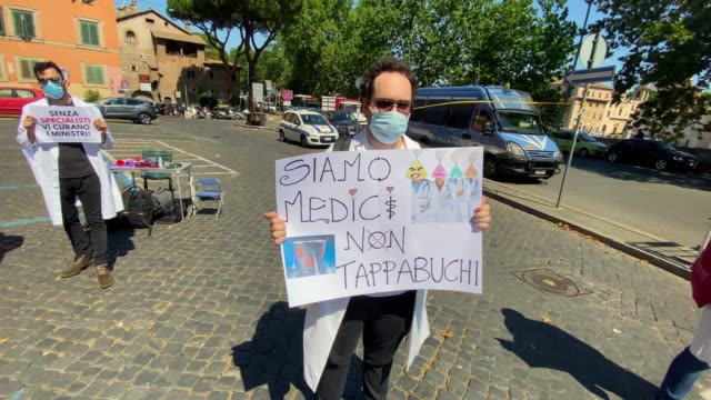 man holds up a sign as young doctors gather together for a demonstration organized by the association for the rights of italian doctors in front of... - new hire stock videos & royalty-free footage