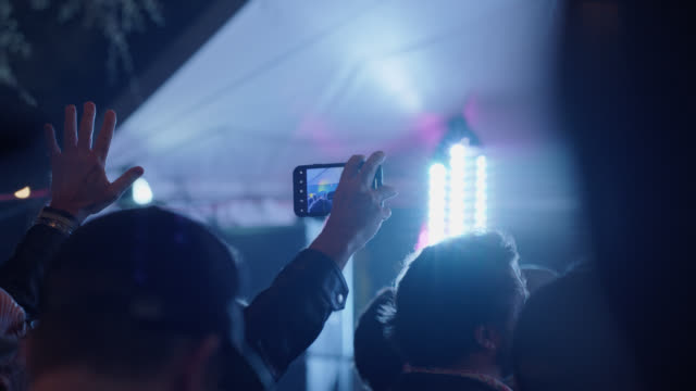 vídeos y material grabado en eventos de stock de man holds up an iphone in the middle of a large crowd to record a hipster cowboy rock band performing at a popular music festival - generación z