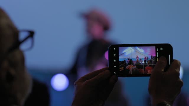 cu. man holds up an iphone to take photos of a hipster cowboy rock band performing at a popular music festival - beatnik stock videos & royalty-free footage