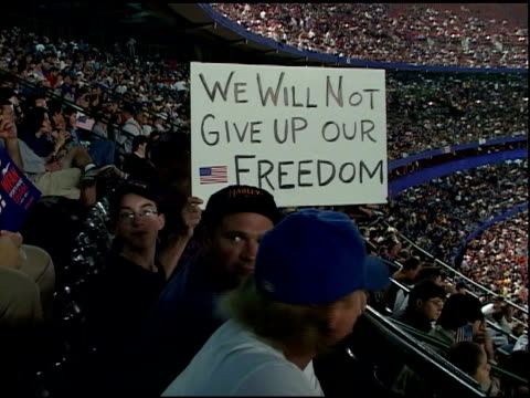 man holds up sign we will not give up our freedom sitting in crowd at shea stadium at first mlb baseball game after september 11 terrorist attacks... - atlanta braves stock-videos und b-roll-filmmaterial