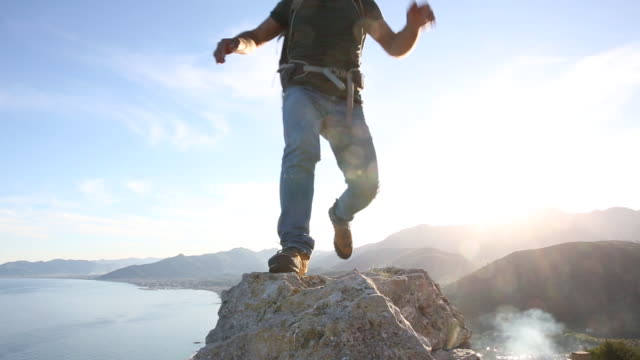 man hops between rocks, walks out to viewpoint above sea - low angle view stock videos & royalty-free footage