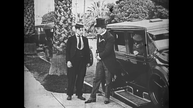 1921 man (buster keaton) hops onto the back of a car and, once it comes to a stop, opens the door for the passengers hoping for a tip - 1921 stock videos & royalty-free footage