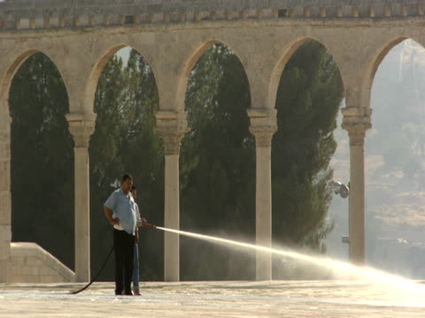 a man hoses down the courtyard in front of the dome of the rock. - gerusalemme est video stock e b–roll