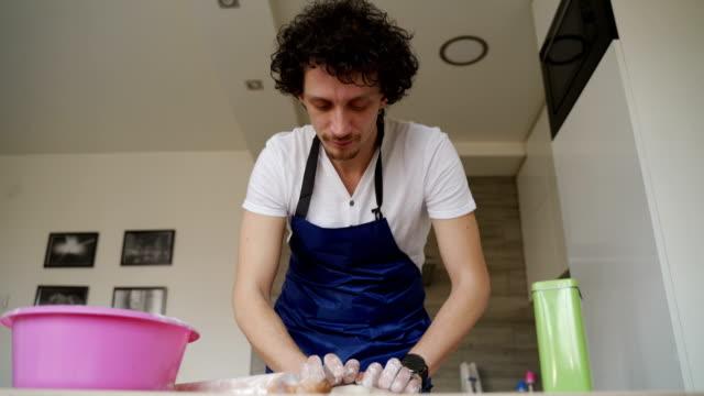vídeos y material grabado en eventos de stock de hombre ama de casa en la cocina preparando una masa de pizza - varón