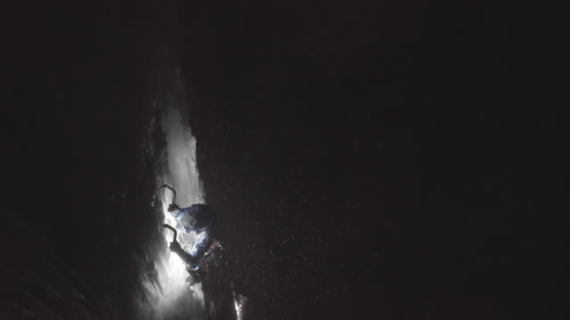 a man ice climbing at night on a frozen waterfall in the mountains. - climbing stock videos & royalty-free footage