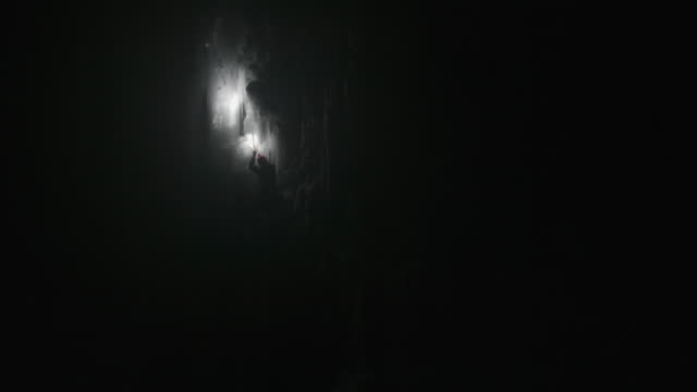 a man ice climbing at night on a frozen waterfall in the mountains. - flashlight stock videos & royalty-free footage
