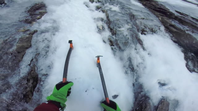 A man ice climbing with ice axes on a snow covered mountain.
