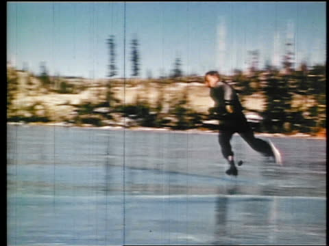 1945 man ice skating on mountain lake / trips + falls / industrial