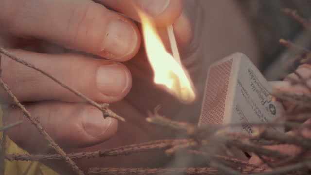 man igniting firewood a small bonfire. close up on hands - burning stock videos & royalty-free footage