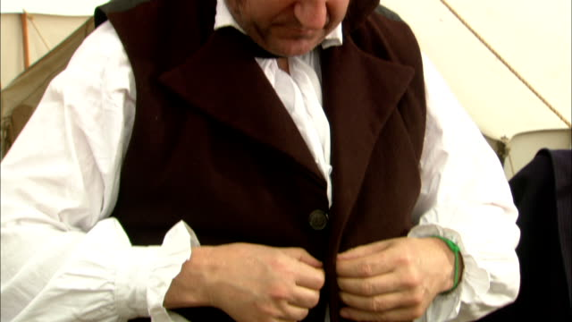 A man in 19th century clothing buttons his waistcoat during a reenactment at The Alamo.