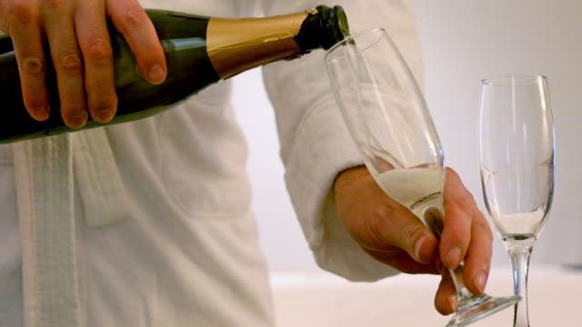 Man in a Bathrobe Pouring Champagne