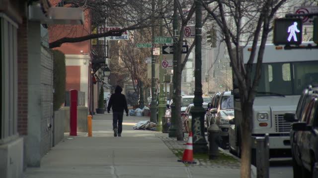 a man in a black hoodie walks down washington street in new york city - schwarzes hemd stock-videos und b-roll-filmmaterial