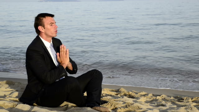 man in a black suit relaxes on the beach. - cravat stock videos and b-roll footage