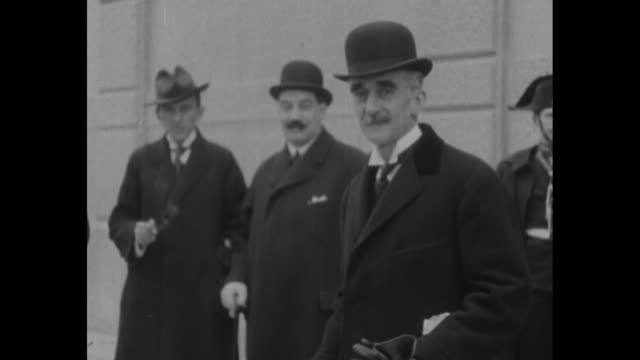 man in a bowler hat briefly poses as two men, one with a cigarette and another with a cane look on; partial view of a uniformed man at right / note:... - moustache stock videos & royalty-free footage