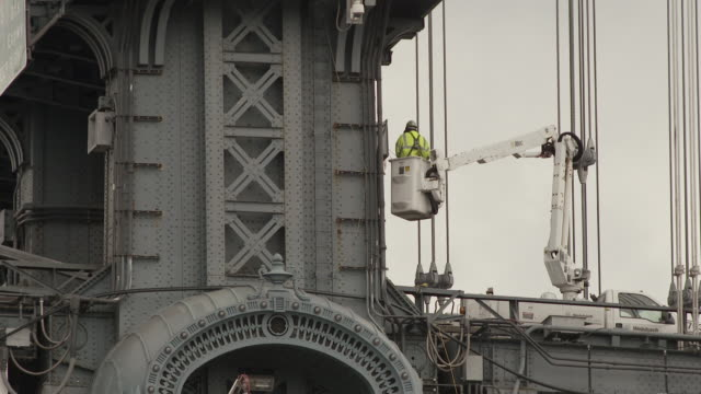 vídeos de stock, filmes e b-roll de a man in a bucket lift works on a electrical box on the outside of the manhattan bridge. - manhattan bridge