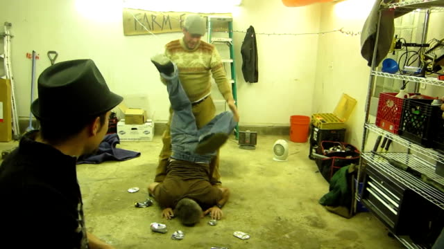 / man in a garage attempts to do handstand with all of his weight on two beer cans / friend helps him lift his legs up and as the beer cans collapse... - sporting term stock videos & royalty-free footage