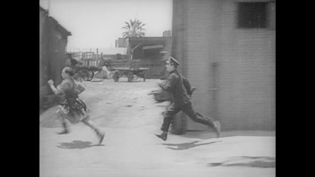 vidéos et rushes de 1922 man (buster keaton), in a gladiator costume, is chased down the street by a policeman - gladiateur