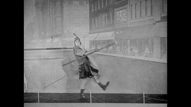 vídeos de stock e filmes b-roll de 1922 man (buster keaton), in a gladiator costume, performs a dance when left alone on stage, and although the audience cheers and laughs, the director pulls him off of the stage with a vaudeville hook and throws him out of the theater - artista