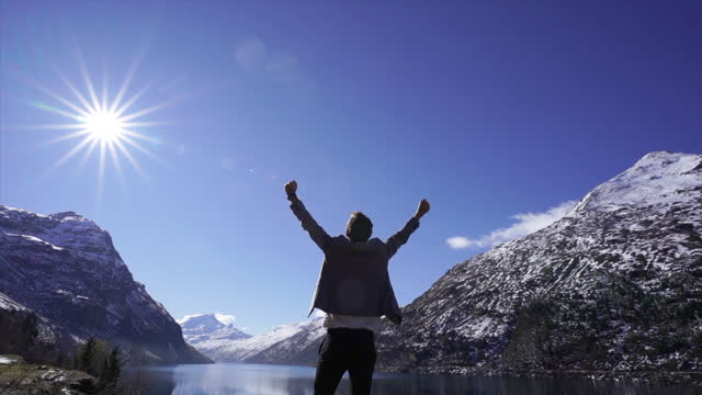 man in a grey suit standing on a rock celebrating with hands in the air near a lake and snowy mountains - offbeat stock videos & royalty-free footage